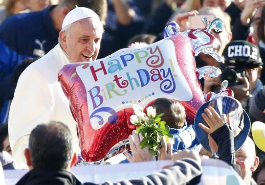 A faithful holds a balloon as Pope Francis, who's 78th birthday is today, arrives to lead his general audience at the Vatican