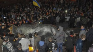People surround a statue of Soviet state founder Vladimir Lenin, which was toppled by protesters during a rally organized by pro-Ukraine supporters in the centre of the eastern Ukrainian town of Kharkiv