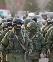 Military personnel, believed to be Russian servicemen, walk outside the territory of a Ukrainian military unit in the village of Perevalnoye outside Simferopol
