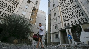 A man walks on rubble near an apartment block damaged by what locals say was shelling by Ukrainian forces in Donetsk