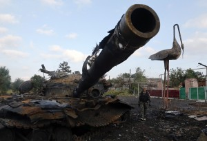 Pro-Russian separatist walks past a destroyed tank at Savur-Mohyla, a hill east of the city of Donetsk