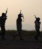 Free Syrian Army fighters carry their weapons as they walk on a frontline in Mork town