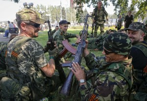 Pro-Russian separatists hold their weapons as they rest after a rally in Donetsk