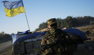 A Ukrainian serviceman stands at a checkpoint in Schastya