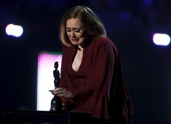 Adele reacts as she accepts the global success award at the BRIT Awards at the O2 arena in London